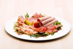 Matmagasin med läcker salami, stycken av skivad skinka, korven, tomater, sallad och grönsaken - royaltyfria foton