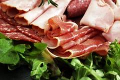 Matmagasin med läcker salami, stycken av skivad skinka, korven, tomater, sallad och grönsaken - köttuppläggningsfat med val Royaltyfria Bilder