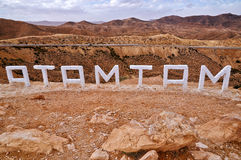 Matmata town sign. Rear view of Matmata town sign with rocky desert landscape and mountains in background, Tunisia Stock Photography