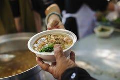 Matning det fattigt till händer av en tiggare Armodbegrepp royaltyfria foton