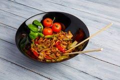 Maträtt för traditionell kines på en rund platta, risnudlar, en grön kål för kål och stekte grönsaker, röda körsbärsröda tomater arkivfoton
