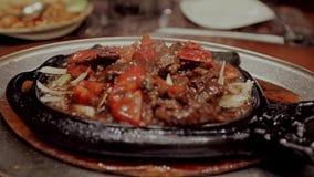 Maträtt i en varm kastrull i restaurangen lager videofilmer