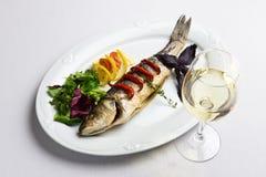 Maträtt med den bakade fisken och winen Arkivfoton