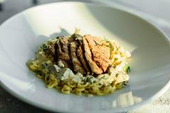 Maträtt med köttstycken, pasta, gräsplaner och sås från gras för en foie royaltyfri foto
