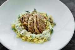 Maträtt med köttstycken, pasta, gräsplaner och sås från gras för en foie arkivbild