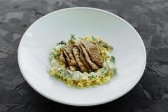 Maträtt med köttstycken, pasta, gräsplaner och sås från gras för en foie arkivfoto