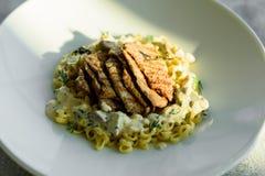 Maträtt med köttstycken, pasta, gräsplaner och sås från gras för en foie royaltyfria bilder