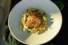 Maträtt med köttstycken, pasta, gräsplaner och sås från gras för en foie royaltyfri fotografi