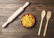 Maträtt med makaroni tillsammans med gaffel av trä och en rulle på tabellen av trä Arkivbilder