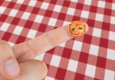 Maträtt med pizzamargherita i miniatyr på fingret royaltyfri bild