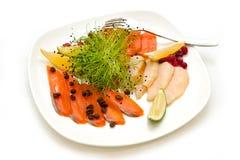 Maträtt med skivat?? röd fisk med citrusa kaffebönor och bär arkivfoto