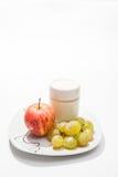 Maträtt med yoghurt, äpplet och druvor arkivbild
