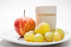 Maträtt med yoghurt, äpplet och druvor royaltyfri foto