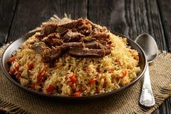 Maträtt, ris är förberedda med grönsaker, och kött för pilaff som traditionell asiatisk Arkivfoto