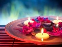 Maträttbrunnsort med att sväva stearinljus, orkidé, i trädgård Royaltyfri Foto
