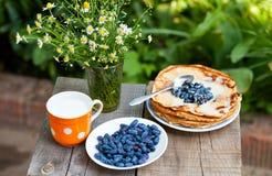 Maträtten är läckra vikta pannkakor med ny bär och sås Royaltyfri Bild