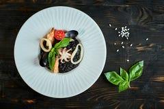 Maträtten av risotto med tioarmad bläckfiskfärgpulver på grå färger pläterar jpg Arkivbild