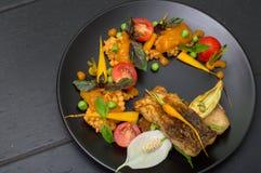 Maträtten från stekt fisk med linser, gröna ärtor, aprikossås, behandla som ett barn morötter och körsbärsröda tomater Svart träb Arkivbild