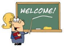 Maître d'école féminin blond indiquant la bienvenue en fonction Images libres de droits