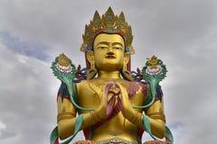 Matreia的菩萨一个巨大的金黄雕象用他的手在他的在富有的装饰的胸口和冠折叠了反对多云的灰色 库存图片