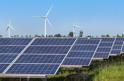Matrice di file dei pannelli solari policristallini e dei generatori eolici del silicio che generano elettricità nella stazione i Fotografia Stock