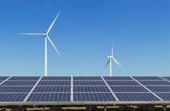 Matrice di file dei pannelli solari policristallini e dei generatori eolici del silicio che generano elettricità nella stazione i Immagini Stock