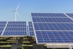 Matrice di file dei pannelli solari policristallini e dei generatori eolici del silicio che generano elettricità nella stazione i Fotografie Stock Libere da Diritti