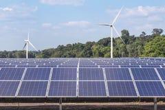 Matrice di file dei pannelli solari policristallini e dei generatori eolici del silicio che generano elettricità nella stazione i Immagine Stock