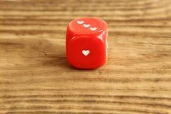 Matrices/cube rouges avec des coeurs sur le fond en bois Photographie stock libre de droits