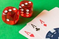 Matrices, jetons de poker et cartes de jouer sur la table verte L'escroquerie photo stock