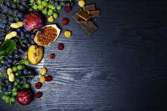 matrich med resveratrol, druvor, plommoner, goji, jordnötter, tranbär, raspberryschoklad på svart träbakgrund fotografering för bildbyråer