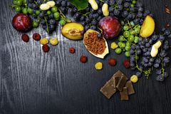 matrich med resveratrol, druvor, plommoner, goji, jordnötter, tranbär, raspberryschoklad på svart träbakgrund royaltyfri bild