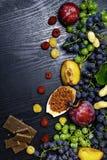 matrich med resveratrol, druvor, plommoner, goji, jordnötter, tranbär, raspberryschoklad på svart träbakgrund royaltyfri foto