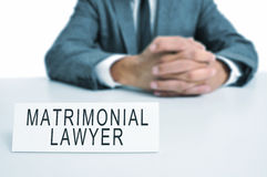 Matrimonial lawyer. A man wearing a suit sitting in a desk with a desktop nameplate in front of him with the text matrimonial lawyer royalty free stock photography
