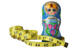 Matrioska Diet. A thin Matrioska doll with a measuring tape Royalty Free Stock Photography
