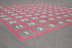 Matrix auf Asphalt mit weißen Zahlen und roten Linien Stockbild