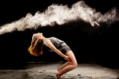 Matrix powder dance pose. Female dancer flexing backwards in a matrix position to avoid the powder Stock Images