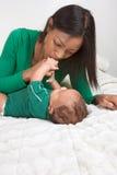 Matriz étnica que joga com seu filho do bebé na cama imagens de stock royalty free