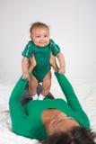 Matriz étnica que joga com seu filho do bebé na cama imagem de stock royalty free