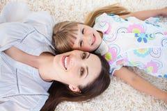 Matriz alegre e sua filha que encontram-se no assoalho Fotos de Stock Royalty Free