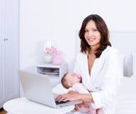 Matriz com bebê e com portátil em casa Foto de Stock Royalty Free