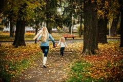 Matriz com a filha no parque do outono Imagens de Stock
