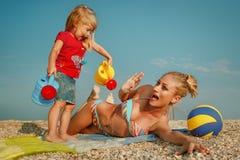 Matriz com a filha pequena na praia Fotos de Stock