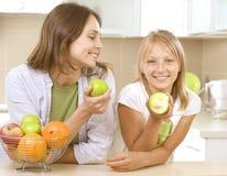 Matriz com a filha que come maçãs Foto de Stock