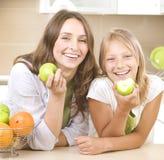 Matriz com a filha que come maçãs Fotos de Stock