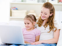 Matriz com a filha que olha o portátil Imagem de Stock