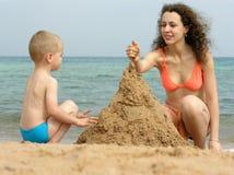 Matriz com jogo do filho na praia Fotografia de Stock