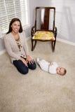 Matriz com o bebê idoso de seis meses em casa Foto de Stock
