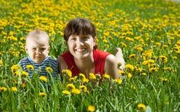 Matriz com o bebê no prado do dente-de-leão Imagens de Stock
