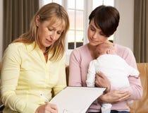 Matriz com o bebê que fala com visitante da saúde Foto de Stock
